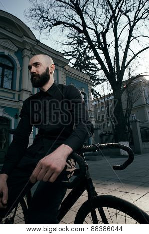 guy with beard in black clothes sits on fix bike