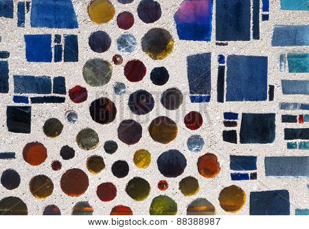 Colorful glass stones in a gray wall