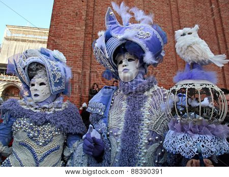 Masked Persons In Magnificent Lilac Costume During The Carnival In Venice, Italy.