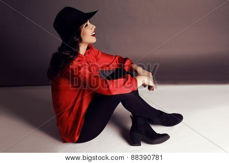 Beautiful Girl With Dark Hair In Elegant Red Blouse And Black Hat