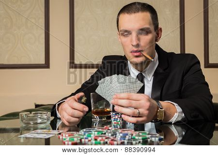 Young Poker player guy in the casino at the gaming table