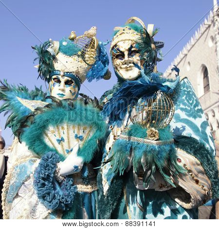 Masked Persons In Magnificent Turquoise Costume During The Carnival In Venice, Italy.