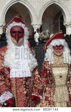 Masked Persons In Magnificent Red And Gold Costume On San Marco Square During The Carnival In Venice
