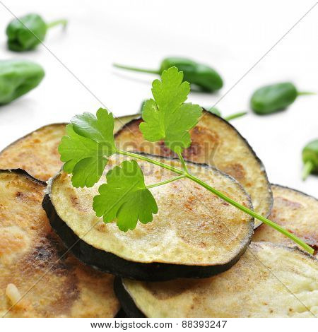closeup of a plate with a pile of appetizing eggplant chips