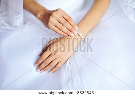 Bride's hands with manicure on the white wedding dress