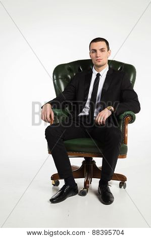 Male businessman sitting on a green leather chair on a white background