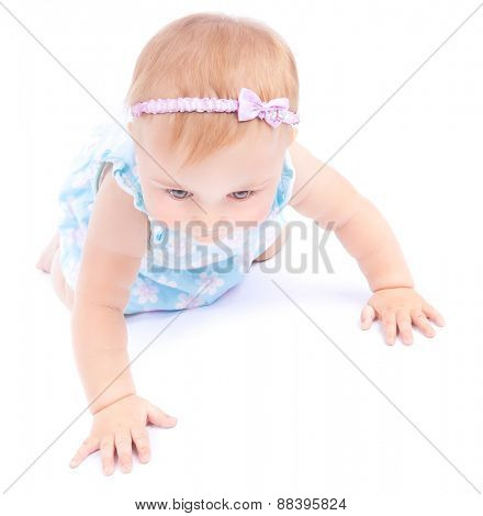 Cute little baby crawling in the studio over white background, small nice child having fun indoors, playful and carefree childhood