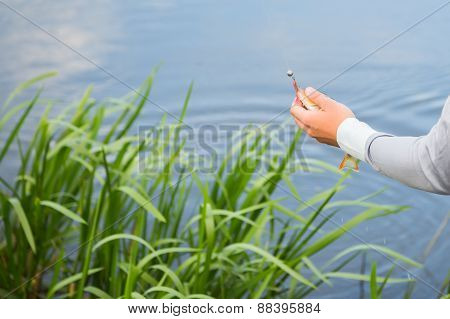 Fisherman with a fishing rod on the river bank.