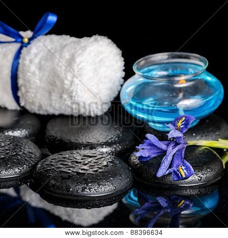 Beautiful Spa Concept Of Blooming Iris Flower, Candle, White Towel And Black Zen Stones On Ripple Re