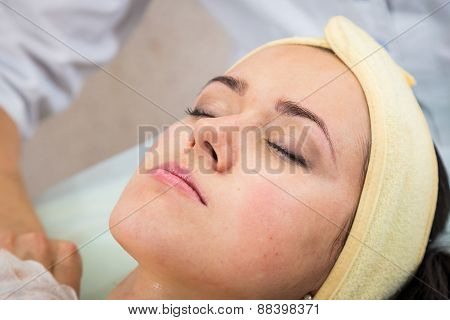 Cosmetic injection in the spa salon. Beautician makes injection into the patient's face
