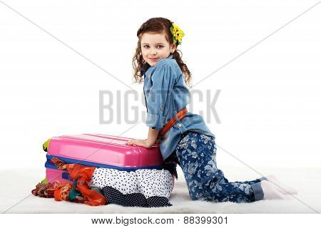 Fashionable Little Girl Closes The Suitcase With Clothes