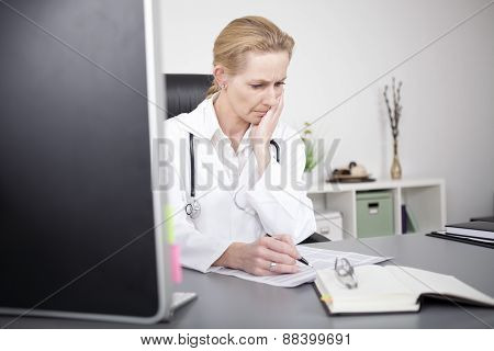 Female Clinician Reading Medical Reports Seriously