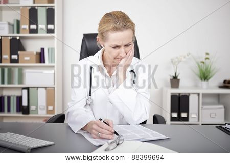 Thoughtful Female Doctor Studying Medical Findings