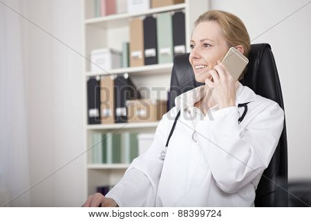 Smiling Female Doctor Calling On Mobile Phone