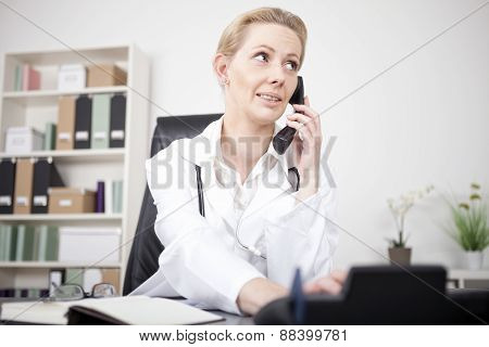 Serious Female Doctor Calling Through Telephone