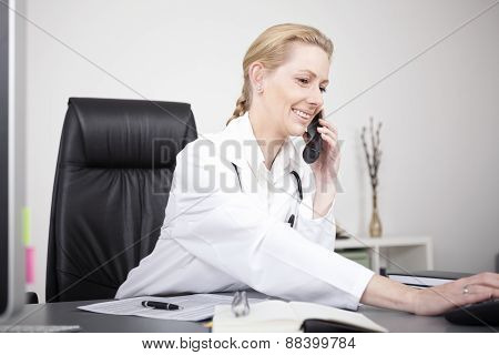 Happy Female Doctor Calling Through Telephone