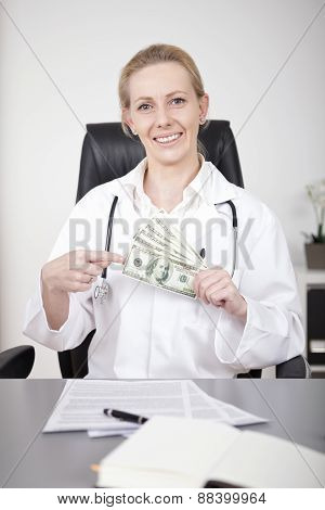 Smiling Female Physician Showing A Fan Of Dollars