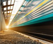 pic of passenger train  - High speed passenger train on tracks with motion blur effect at sunset - JPG