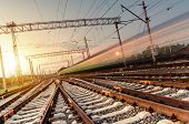 stock photo of passenger train  - High speed passenger train on tracks with motion blur effect at sunset - JPG