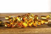 picture of prophylactic  - yellow dietary supplement pills on wooden desk - JPG