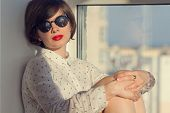 foto of daydreaming  - Girl with sunglasses daydreaming sitting by the window - JPG