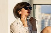 image of daydreaming  - Girl with sunglasses daydreaming sitting by the window - JPG