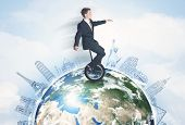 stock photo of unicycle  - Man riding unicycle around the globe with major cities concept - JPG