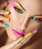 foto of long nails  - Beauty Girl face with Vivid Makeup and colorful Nail polish - JPG