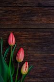 image of bouquet  - Red tulips flowers bouquet on old wooden table background - JPG