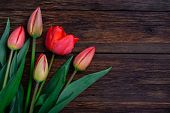 stock photo of bittersweet  - Red tulips flowers bouquet on old wooden table background - JPG