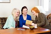 picture of memento  - Three Happy Middle Age Women Sitting at the Living Area Looking at their Old Photograph in a Photo Album.
