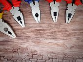 picture of pliers  - copyspace image set of handtools pliers on vintage wooden board construction concept - JPG