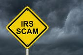 stock photo of irs  - IRS Scam Warning Sign Yellow warning road sign with word IRS Scam with stormy sky background - JPG