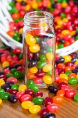 stock photo of jar jelly  - Jelly beans in a glass jar with a spilled basket of jelly beans behind it - JPG