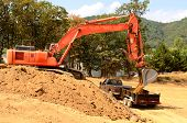 stock photo of track-hoe  - Exchavator track hoe loads a small dump trailer with top soil and loose dirt at a new commercial construction development project - JPG