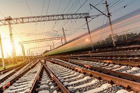 image of passenger train  - High speed passenger train on tracks with motion blur effect at sunset - JPG