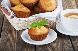 foto of bakeshop  - Homemade muffins and a cup of tea with lemon on wooden background - JPG