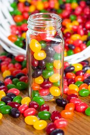 picture of jar jelly  - Jelly beans in a glass jar with a spilled basket of jelly beans behind it - JPG