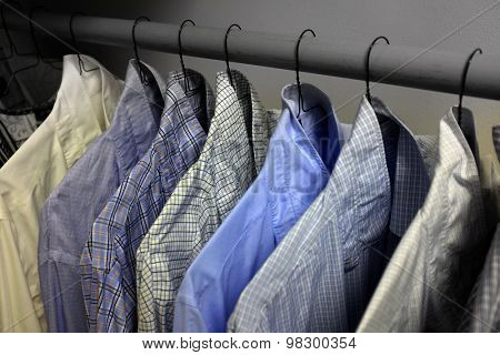 Row of dress shirts hanging on hangers in closet choice of clothing