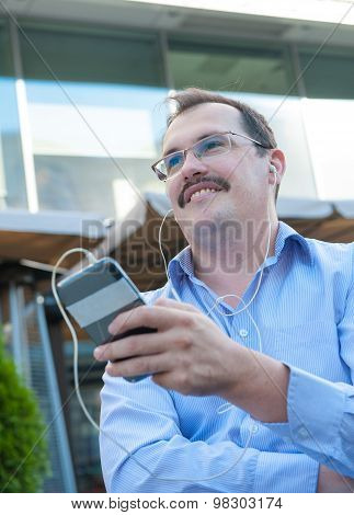 Urban man using smart phone outside using app on 4g wireless device wearing headphones. Adult urban