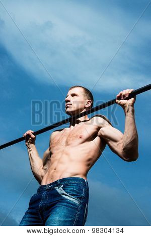Closeup Of Strong Athlete Doing Pull-up On Horizontal Bar. Mans Fitness With Blue Sky In The Backgro