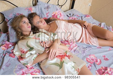 blond sisters or sexy girl friends having fun relaxing in pajamas lying on white bed looking at came