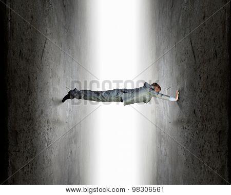 Businessman under pressure between two stone walls