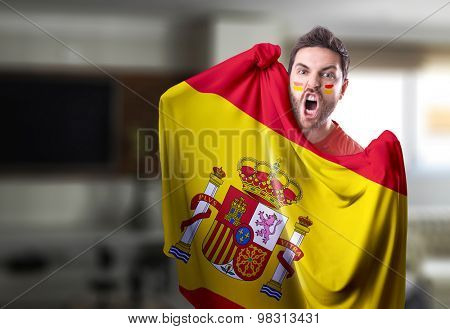 Fan holding the flag of Spain at home