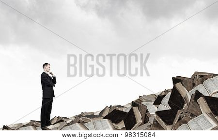 Thinking businessman with hand on chin on pile of old books