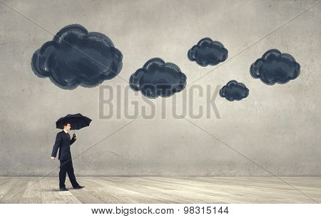 Walking businessman with black umbrella and black cloud above