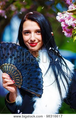 Beautiful Girl with flowers, glamour white fur and black fan in hand, posing next to blooming magica