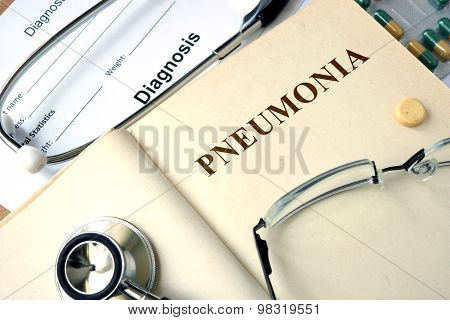 Word  Pneumonia on a paper and pills.