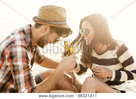 Young couple at the beach having fun, laughing and drinking beer