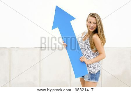 Young and beautiful girl  holding a blue arrow